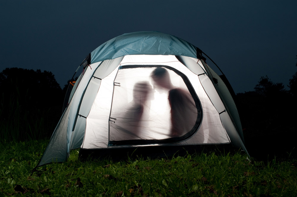 Couple of campers in a tent getting romantic