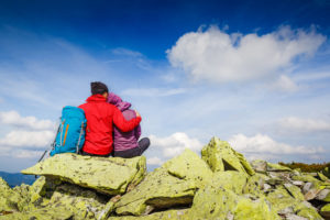 Two hikers snuggling on top of a mountain after a cool weather hike